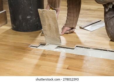 Carpenter Applying Parquet Glue