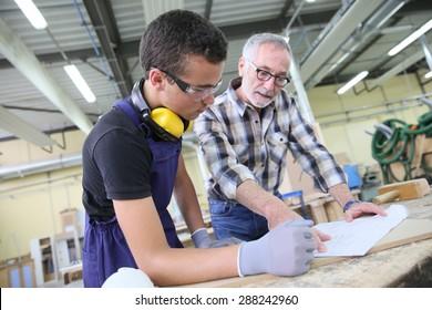 Carpenter with apprentice in training period