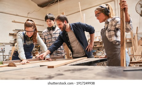 Carpenter apprentices with trainers at the circular saw in the carpentry workshop