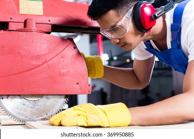Carpenter in Asian workshop with circular saw in a manufacturing factory