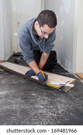 Carpenter bending down in a passage measuring new wooden floor boards during renovations and construction