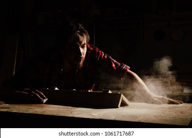 carpenter blows off wood dust cloud by wooden billet. Adult men joiner, red checkered shirt, jeans. dark background.