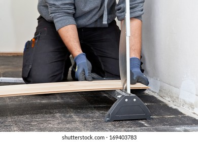 Carpenter or builder measuring and cutting a new wooden floor board for installation during renovation or construction of a building
