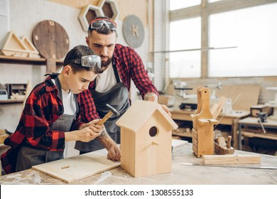 Carpenter building a wooden birdhouse together with his kid. A little son is participating actively in hand made process. Happy fatherhood and DIY concept.