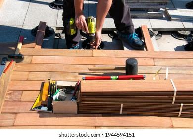 Carpenter building wooden deck construction, Ipe wood deck installation worker, decking hardwood terrace