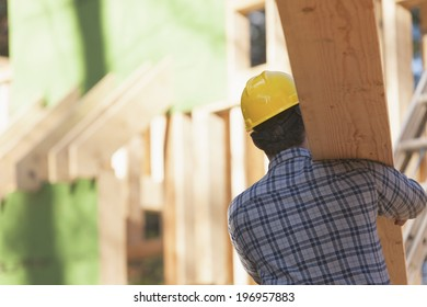 Carpenter carrying roof rafters on his shoulder