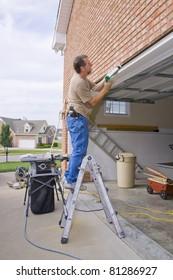 Carpenter caulking cracks between garage door frame and brick