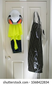 Carpenter and chef uniforms hanging at the door next to each others