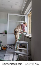 carpenter cleaning the workplace after replacing a window