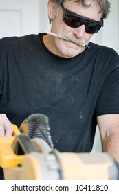 a carpenter concentrating on making the correct cut - focus on mouth in concentration