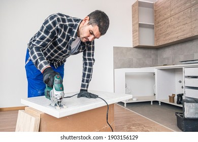 A carpenter with a corded jigsaw cutting a part of the wooden surface (board) intended for the shelves of the kitchen hanging element.