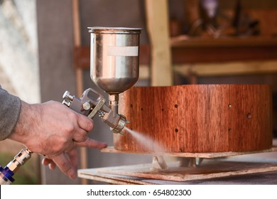 Carpenter covering wooden drum with lacquer