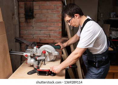 Carpenter cuts a piece of plywood with a miter saw. The man is dressed in working clothes gray overalls and a white T-shirt