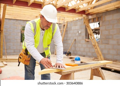 Carpenter Cutting House Roof Supports On Building Site