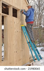 Carpenter cutting openings in plywood sheathing for windows