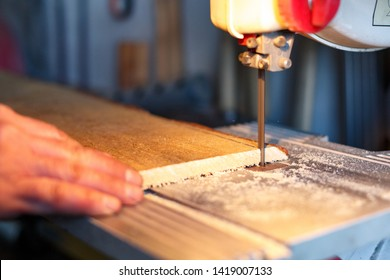 Carpenter Cutting a Piece Of Wood With Bandsaw In Workshop