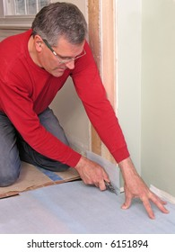 Carpenter cutting underlayment for flooring