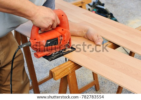 Carpenter cutting a wooden panel for wooden floor with the jigsaw, carpentry tools