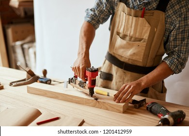 Carpenter doing his job in carpentry workshop, drilling a hole with an electrical drill in workshop. Profession, carpentry, woodwork and people concept.