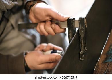 Carpenter doing his job in carpentry workshop. Close up