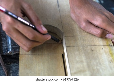 Carpenter drawing curve line of wooden board with pencil and tamplate