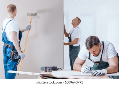 Carpenter drawing on a fiberboard and painter with toolbelt painting the wall during interior finishing work