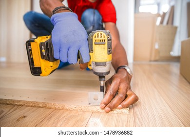 A carpenter drilling screws into a cupboard door.