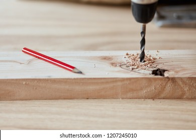 Carpenter drills a hole with an electrical drill on a wooden plank with red pensil, close up.