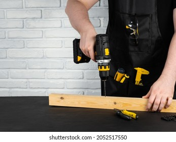 A carpenter drills a hole in a wooden board with an electric drill. Close-up of hands of a foreman at work. Working environment in a carpentry workshop. Cordless cordless drill - screwdriver with dril