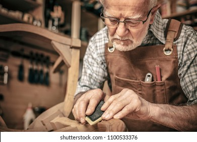 carpenter engaged in polishing an unfinished chair