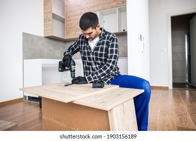 The carpenter finalizing the assembly of the kitchen shelf on the floor.