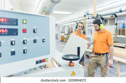 Carpenter in furniture factory inspecting piece in QA being satisfied