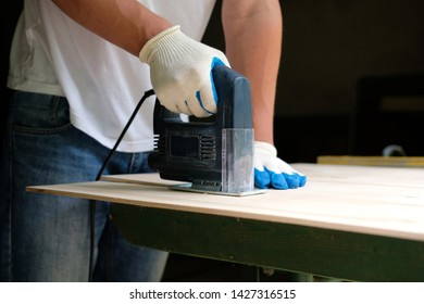 Carpenter in gloves using jig saw in workshop. Side view.