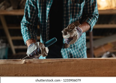 Carpenter with a hammer and chisel handles wood. Joiner at work in the workshop. Home workshop, with their hands