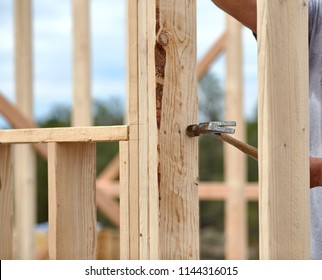 Carpenter hammering a nail into a 2x4 piece of wood on a new wall stud