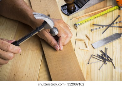 The carpenter hammers nail into a plate on the desktop with tools