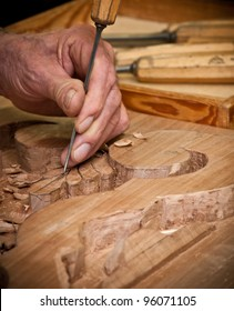 carpenter hand carving wood with care