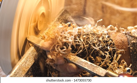 Carpenter handles wood by lathe. Builder works with the workpiece in the workshop. Making beautiful wooden handmade dish. Woodworker cuts wood by chisel. Sawdust fly from detail in soft focus.