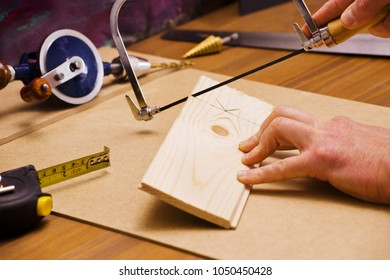 Carpenter has section of pine marked with line and is sawing wood panel. On desk are several construction tools.