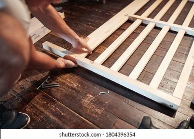 Carpenter hobbyist assembling wooden boards at home / garage.