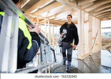 Carpenter Holding Drill Machine While Looking At Colleague Carry