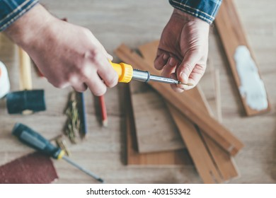 Carpenter holding a screwdriver. Selective focus and small depth of filed.