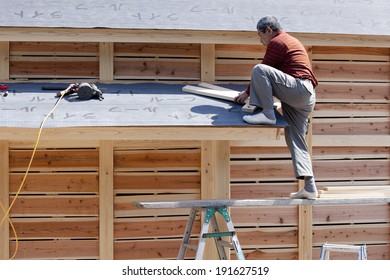 Carpenter and house under construction