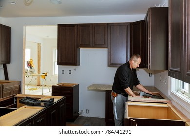 Carpenter installing cabinets and counter top in a kitchen. and partially installed