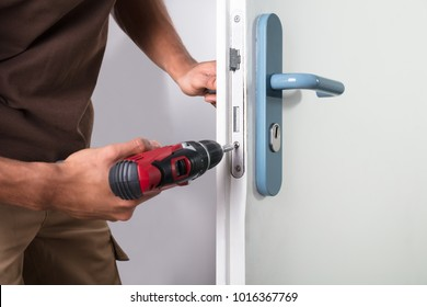 Carpenter Installing Door Lock With Wireless Screwdriver