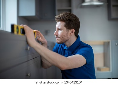 Carpenter Installing Luxury Modern Fitted Kitchen