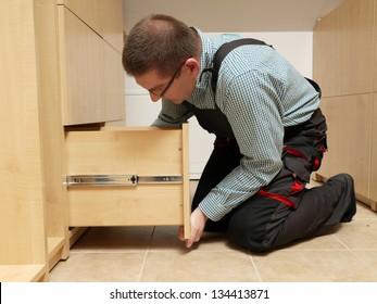 Carpenter installing wardrobe drawers in walk-in closet