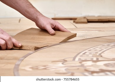 The carpenter installs one of the decorative elements of the parquet.