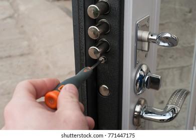 The carpenter installs a reliable burglar-resistant lock in the metal door.