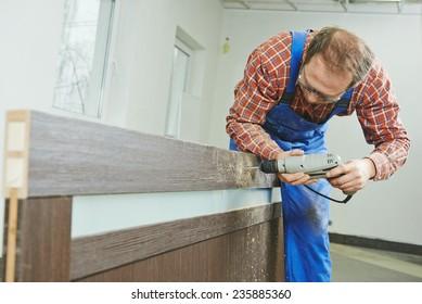 carpenter at interior wood door lock installation working with drill